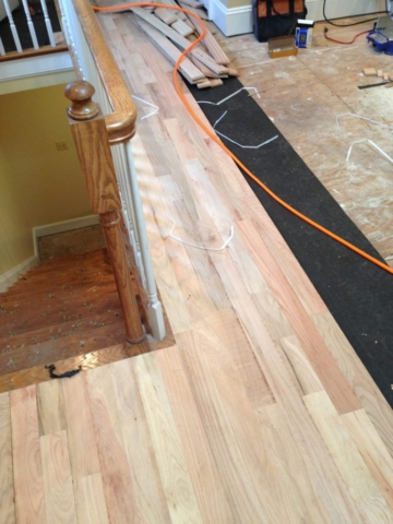 A photo of red oak hardwood installation over tar paper and plywood subflooring.