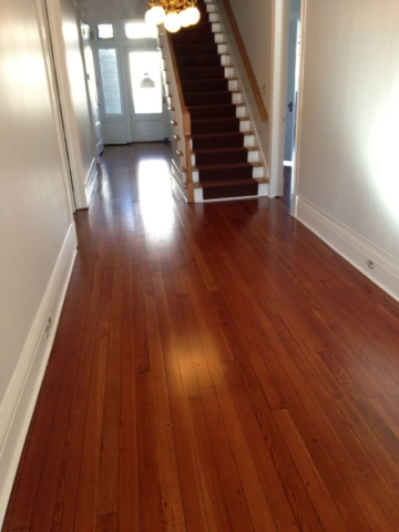Satin finished, smooth, red toned, hardwood floors that were previous cover with tar and tile.