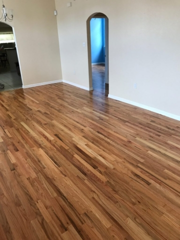 Pictured are red oak floors with a natural finish in a living room with Spanish arched doorways. The contrasting colors in the wood grain are eye catching with shades of red tones, browns, and creamy white.