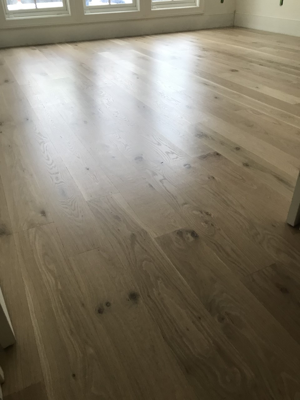 This is a photo of a front room with white oak flooring with a satin finish. It has a weather washed appearance.
