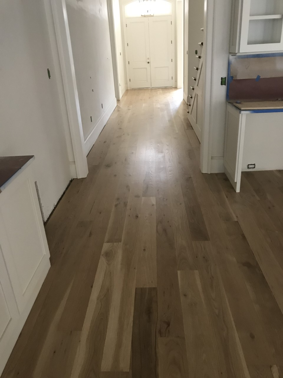 This is a photo of a kitchen with white oak flooring with a satin finish. It has a weather washed appearance.